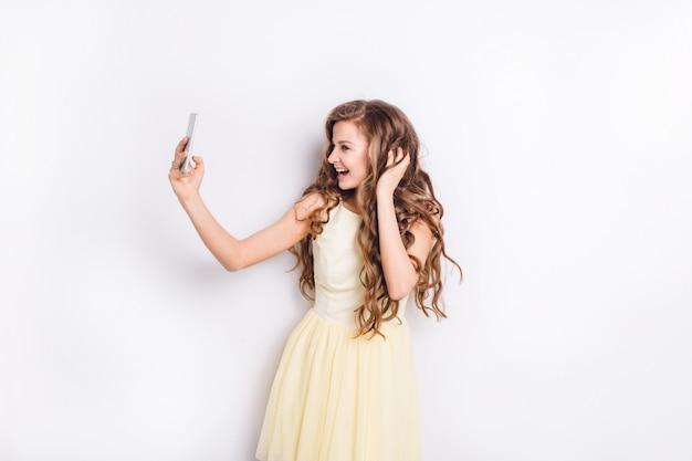 Ładny blond dziewczyna robienie selfie na smartfonie i zabawę. uśmiecha się szeroko i bawi się włosami. nosi żółtą sukienkę. miała długie, kręcone blond włosy