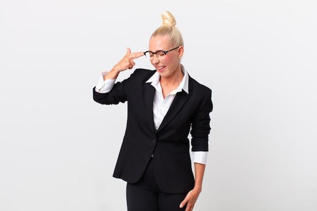 Ładny blond kobieta patrząc niezadowolony i zestresowany, gest samobójczy, co pistolet znak. pomysł na biznes