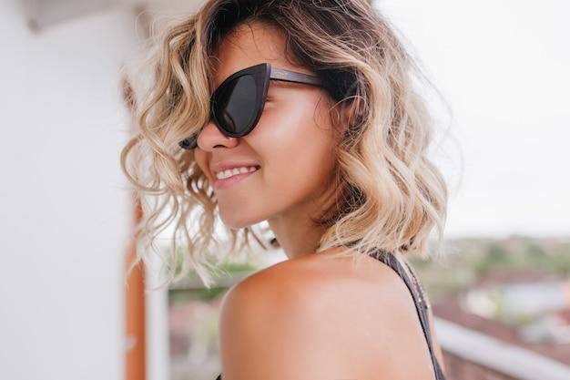 Ładny blond kobieta z zainteresowanym uśmiechem pozowanie. fascynująca krótkowłosa dziewczyna wyrażająca szczęście.
