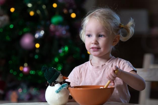 Ładny blond maluch dziewczyna o niebieskich oczach po posiłku w otoczeniu nowego roku. choinka stoi z tyłu. dziewczyna jest leworęczna.