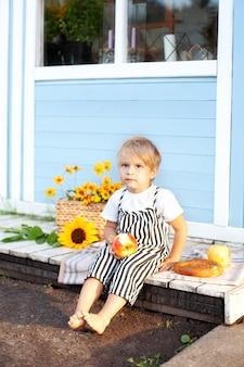 Ładny blond włosy mały chłopiec z jabłkiem i bułką w dłoniach na ganku drewnianego domu na jesienny dzień. letnie wakacje, rekreacja na świeżym powietrzu. koncepcja dzieciństwa. piknik)