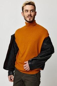 Ładny blondyn w rozpiętej kurtce i pomarańczowym swetrze na jasnym tle