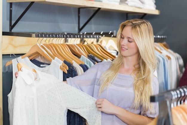 Ładny blondynki kobiety wybierać odziewa w ubrania sklepie