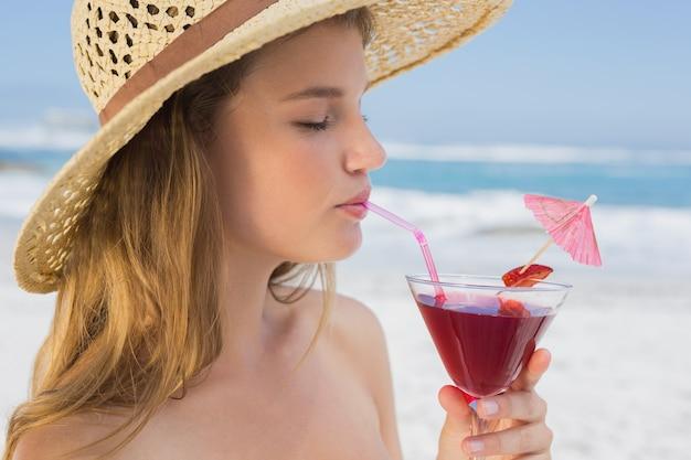 Ładny blondynki popijania koktajl na plaży