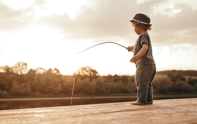 Ładny boso mały chłopiec bawiący się łowienie ryb