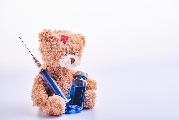 Ładny brązowy miś i fiolka lub ampułki medyczne do wstrzykiwań i strzykawki. niebieska fiolka medyczna i strzykawka w rękach brązowy miś. miś trzyma strzykawkę i ampułkę. odosobniony. skopiuj miejsce