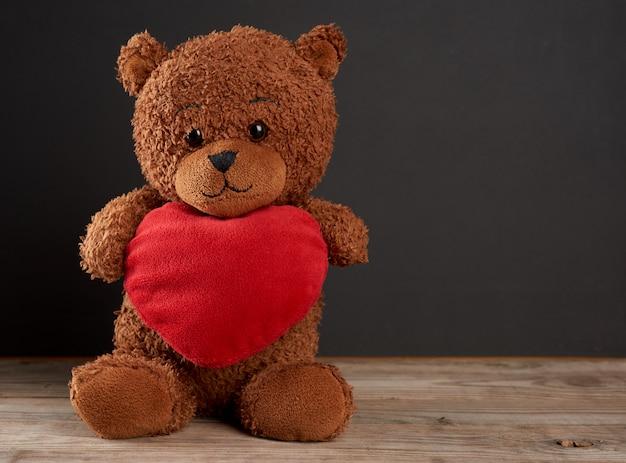 Ładny brązowy miś trzyma duże czerwone serce