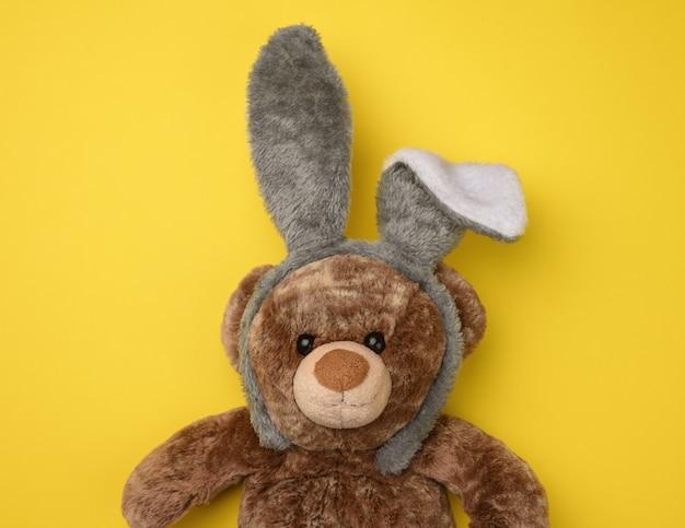 Ładny brązowy miś w masce królika z długimi uszami na głowie, zabawna świąteczna kartka wielkanocna