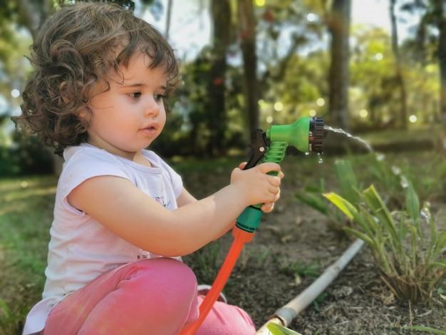 Ładny brazylijski mała dziewczynka zabawy bawiąc się wężem w ogrodzie.