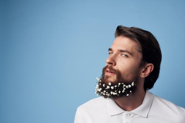 Ładny brodaty mężczyzna kwiaty ozdoba dla zakładów fryzjerskich niebieskie tło.