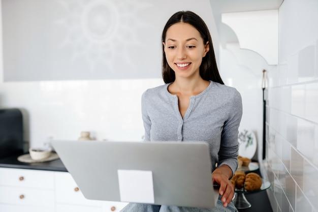Ładny brunetka kobieta siedzi na stole w kuchni i za pomocą laptopa