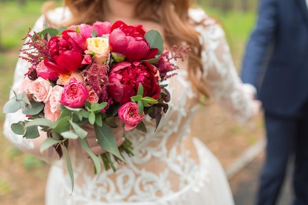 Ładny bukiet ślubny w dłoni młodej pary