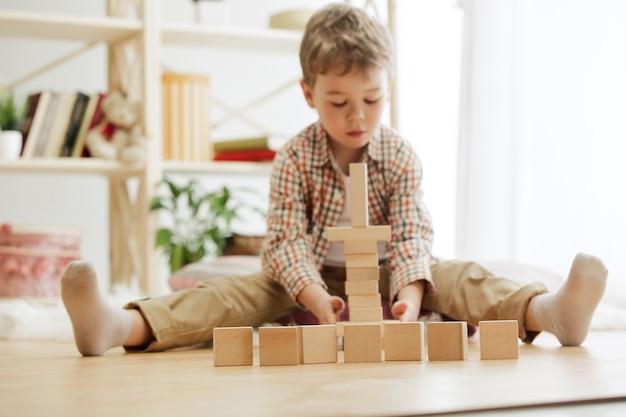 Ładny chłopak bawi się drewnianymi kostkami w domu