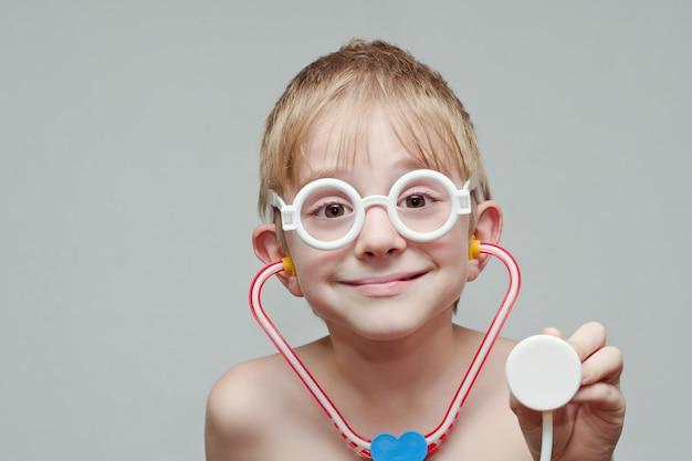 Ładny chłopak bawi się w lekarza. zabawkowe okulary i fonendoskop. portret
