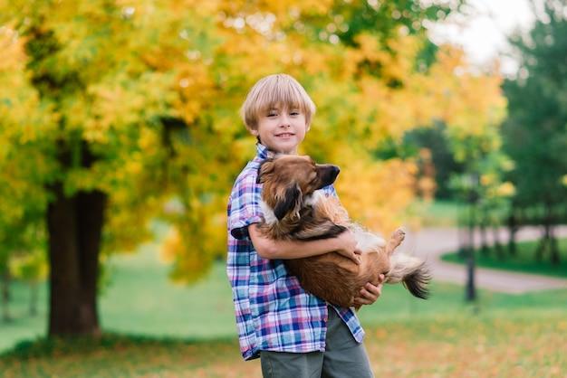 Ładny chłopak gra i spacery z psem na łące.