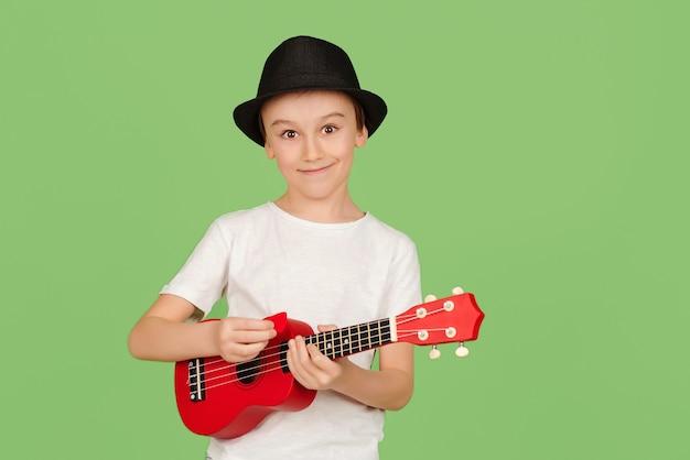 Ładny chłopak gra na ukulele. szczęśliwe dziecko ciesząc się muzyką. uczeń uczący się grać na ukulele. modny chłopak w letnim kapeluszu na białym tle nad zielonym tłem.