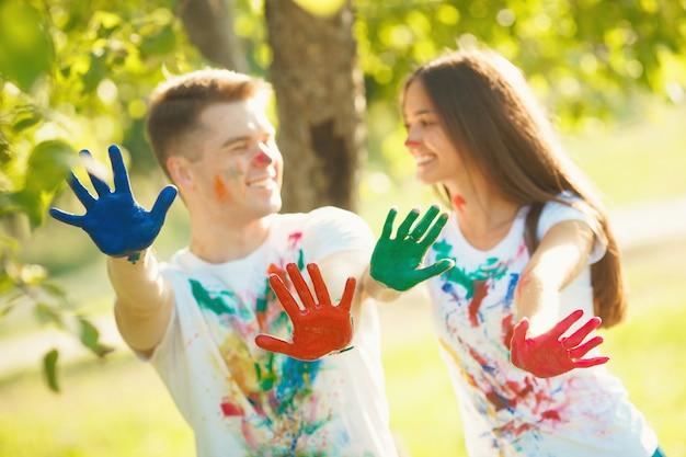 Ładny chłopak i dziewczyna goli ich malowane ręce lub dłonie na aparat i uśmiecha się. przed ustawioną ostrością przed kamerą znajduje się wielobarwne płaskie dłonie ładnej pary.