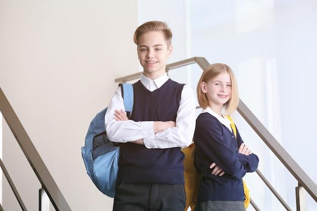 Ładny chłopak i dziewczyna w mundurku szkolnym stojąc na schodach
