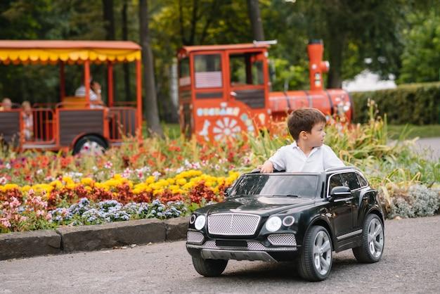 Ładny chłopak jedzie czarnym samochodem elektrycznym w parku