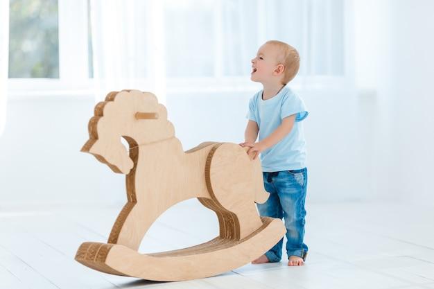 Ładny chłopak na biegunach na drewnianym koniu ręcznie