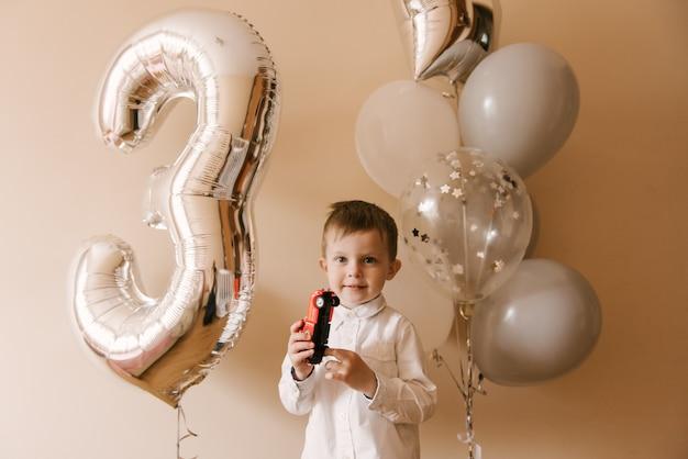 Ładny chłopak obchodzi swoje urodziny, zdjęcie dziecka z balonami