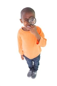 Ładny chłopak patrząc przez szkło powiększające