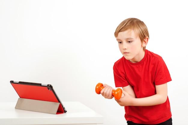 Ładny chłopak robi zdalny trening w domu. dziecko za pomocą nowoczesnego tabletu.