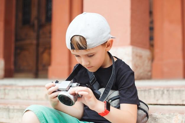 Ładny chłopak robi zdjęcia zabytków. projekt szkolny dla dzieci na letnie wakacje. zawód przyszłości.