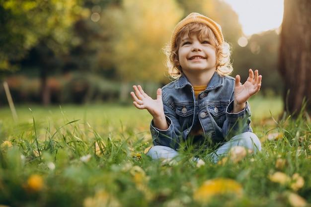 Ładny chłopak siedzieć na trawie w parku