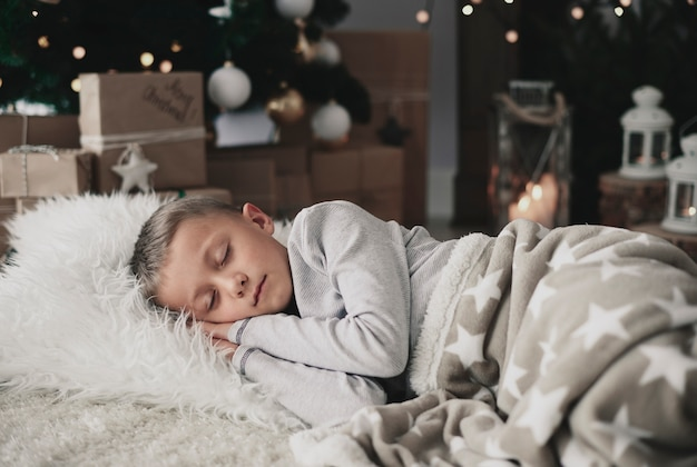 Ładny chłopak śpi na dywanie