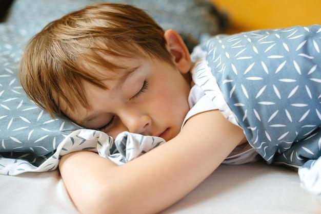 Ładny chłopak śpi w swoim łóżku. poranny czas na przebudzenie.