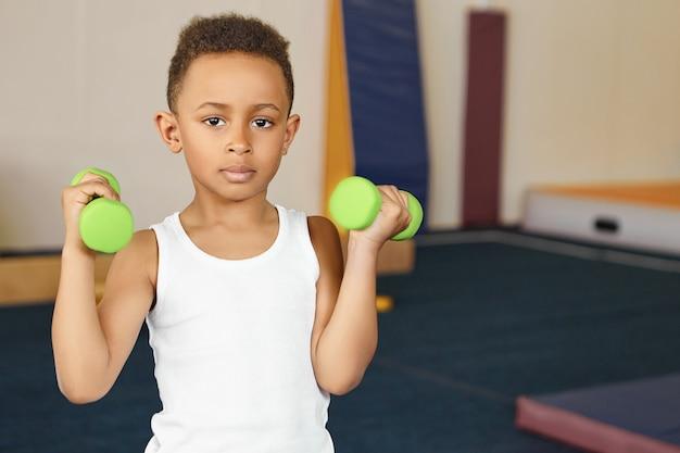 Ładny chłopak sportowiec o afrykańskim wyglądzie robi ćwiczenia fizyczne na siłowni po szkole