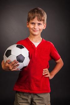 Ładny chłopak trzymając w rękach piłki nożnej