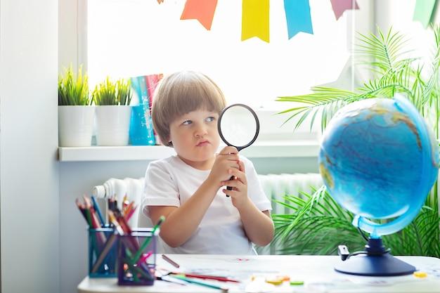 Ładny chłopak w białej koszulce siedzi przy szkolnym biurku, trzymając lupę i patrząc przez nią na kulę ziemską