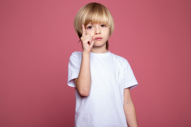 Ładny chłopak w białej koszulce urocze małe dziecko na różowej ścianie