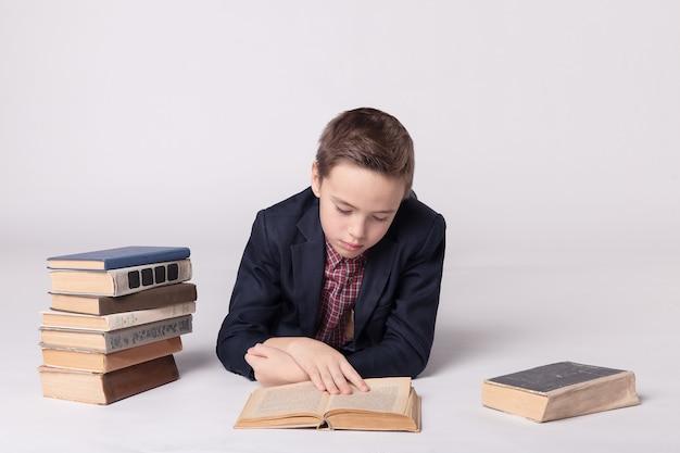 Ładny chłopak w garniturze leży i czyta książkę na białym tle.
