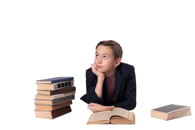 Ładny chłopak w garniturze leży i marzeń na białym tle. stos książek.