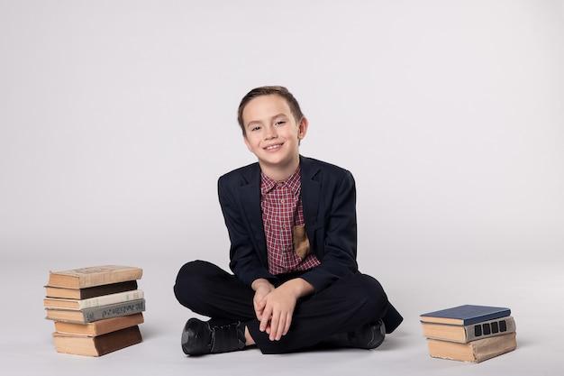 Ładny chłopak w garniturze siedzi na białym tle. stos książek. koncepcja szkoły.
