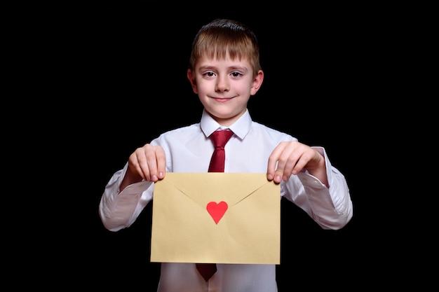 Ładny chłopak w koszulę i krawat trzyma kopertę z sercem. izolować