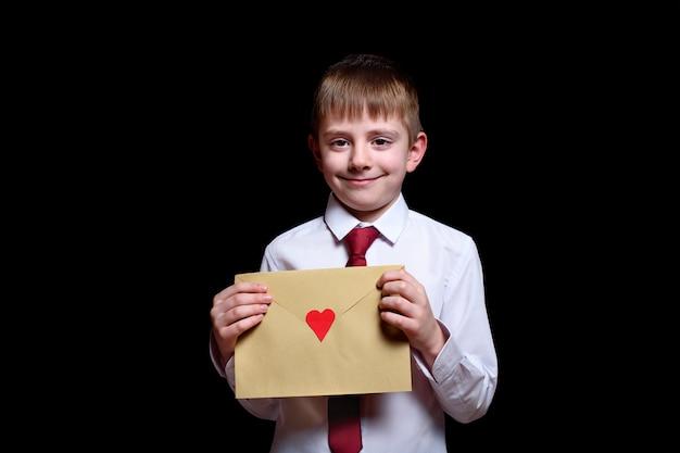 Ładny chłopak w koszulę i krawat trzyma kopertę z sercem