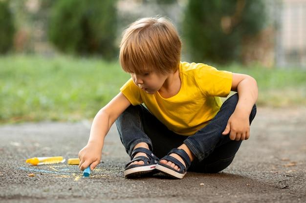 Ładny chłopak w parku, rysowanie kredą