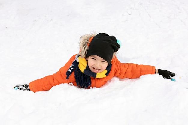 Ładny chłopak w śnieżnym parku na ferie zimowe