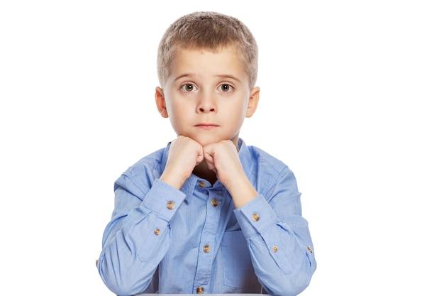 Ładny chłopak w wieku szkolnym z zaskoczony twarz siedzi przy stole. pojedynczo na białym tle.