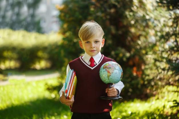 Ładny chłopak wraca do szkoły. dziecko z książkami i kulą ziemską na pierwszy dzień szkolny.