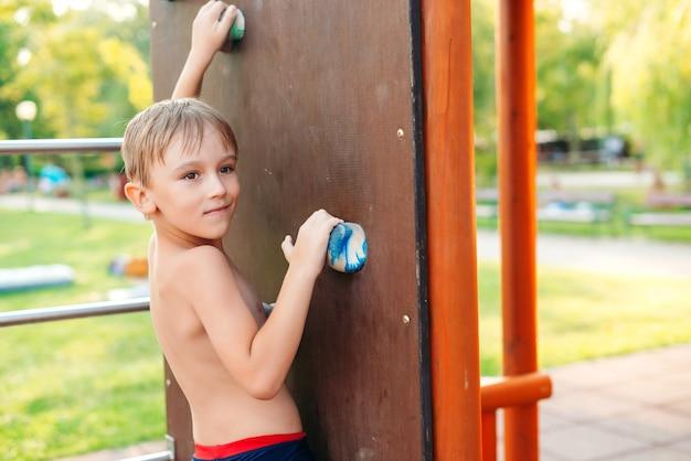Ładny chłopak wspinaczka skalna ściana na placu zabaw na świeżym powietrzu.