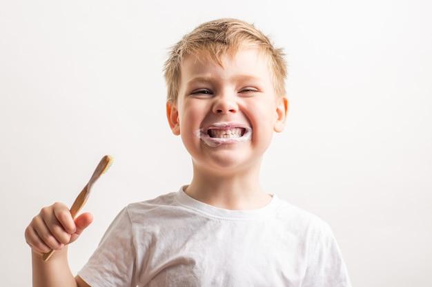 Ładny chłopak z bambusową szczoteczką do zębów w ustach, dziecko myje zęby