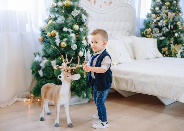 Ładny chłopak z dużym jeleniem zabawka. dziecko na tle urządzonego pokoju bożego narodzenia. święto nowego roku. boże narodzenie i nowy rok.