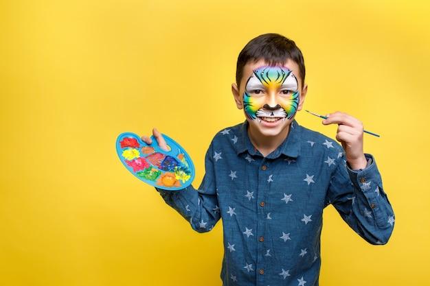 Ładny chłopak z faceart na przyjęcie urodzinowe, kolorowy tygrys trzymając paletę z gwaszem na białym tle na żółtej ścianie.