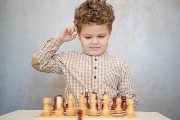 Ładny chłopak z kręconymi włosami gra w szachy przy stole. proces gry w szachy
