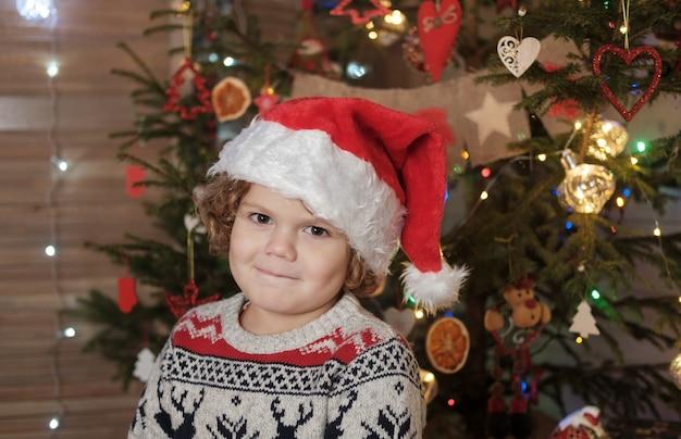 Ładny chłopak z kręconymi włosami w czerwonym kapeluszu santa na choince. koncepcja bożego narodzenia i nowego roku